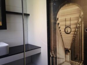 Salle de bains avec papier peint trompe-l'oeil sur porte